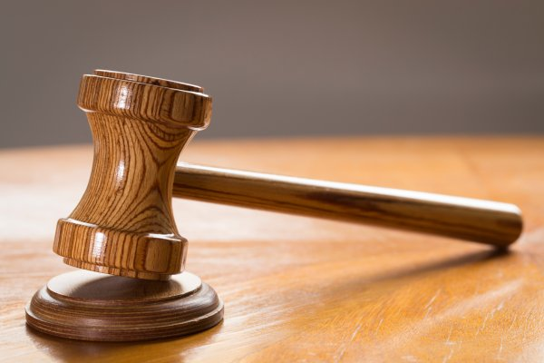 Close-Up Of Wooden Gavel On Table In Courtroom