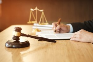 Cropped Hand Of Lawyer Writing On Document At Table In Office