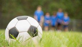 Children's soccer team players run toward ball on playing field.