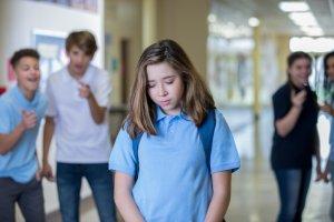 Sad teen female being bullied in hallway