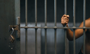 Midsection Of Prisoner Holding Railing While Standing In Prison