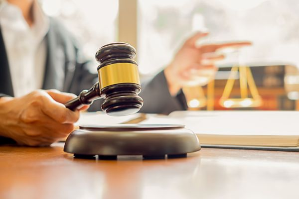 Close-Up Of Judge Holding Gavel On Table
