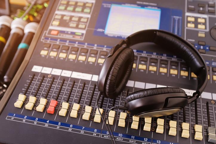 Headphones, microphones, amplifying equipment, Studio audio mixer knobs and faders, background sound mixer. Workplace and equipment sound engineer. Sound acoustic music mixing, selective focus