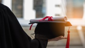 Midsection Of Woman In Graduation Gown Holding Diploma And Mortarboard In City