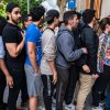 A group of young people stand in a queue to access the...