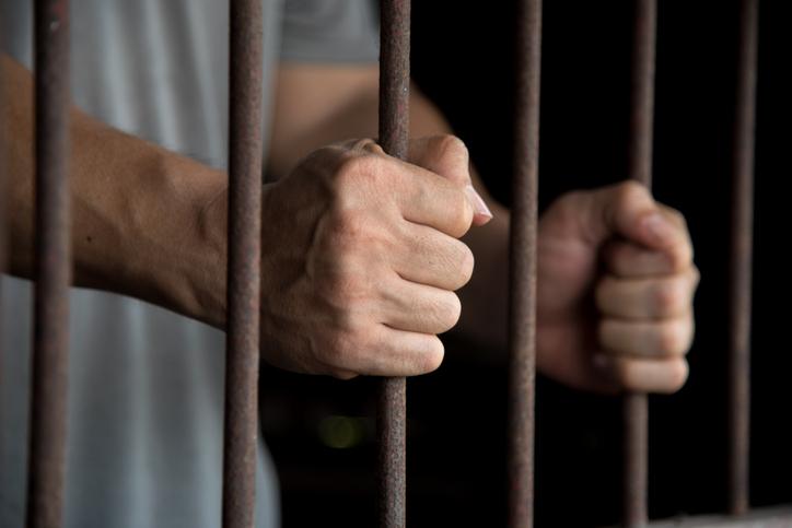 Close-Up Of Man Holding Prison Bars