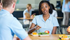 African American teenage girl eats lunch with friends in school cafeteria