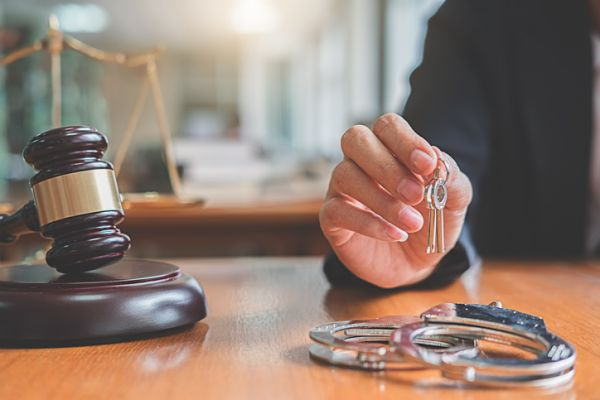 Close-Up Of Judge Holding Keys With Handcuffs On Table
