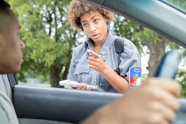 Female police officer discusses traffic laws with driver