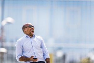 Cheerful African American businessman laughing on the street.