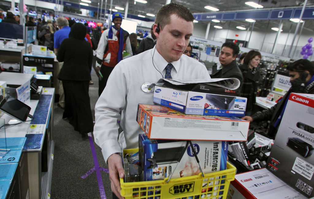 Profile of Mike Ersfeld, general manager of a Best Buy store in Eden Prairie, as copes with the pressure of Black Friday shopping. Ersfeld hands out store maps to customers waiting in line outside the store, greets them as they enter at midnight, and ans