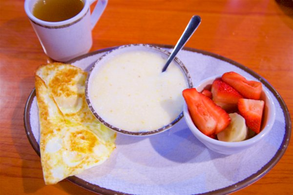 Grits, eggs, strawberries, bananas, and tea for breakfast in New Orleans