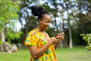 Beautiful african female feeling happy and use smartphone or cellphone with Green background and bokeh