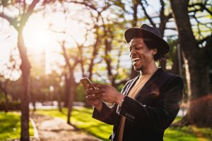 Man using phone in park at sunset