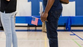 Unrecognizable man holds US flag while waiting to vote