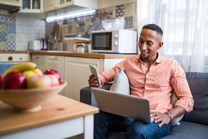 Afro latino men working on a laptop and using smart phone at home
