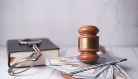 Close Up Of Gavel, Cash And Handcuff On Table