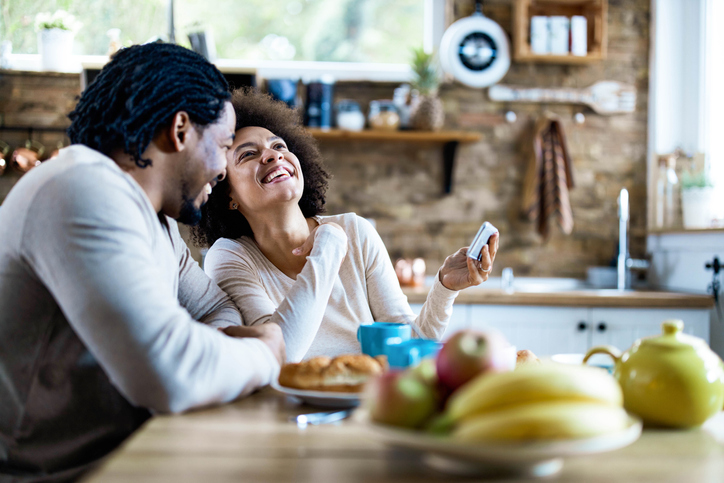 Happy African American couple having fun during morning in dining room.
