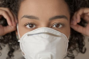 Close-Up Portrait Of Woman Wearing Pollution Mask
