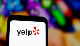 In this photo illustration a Yelp logo seen displayed on a...