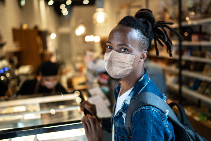 Portrait of young customer with face mask in coffee shop