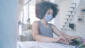 Businesswoman with protective face mask at work, during COVID-19