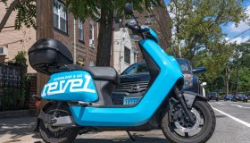 A Revel moped is parked unused on the street in the Queens...
