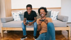 Father With Son Playing Video Game At Home
