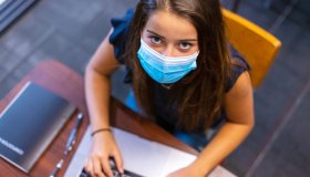 Female High School Student in Classroom Setting Wearing Mask