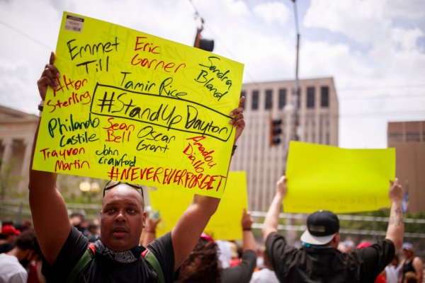 A man holds a sign with the names of people killed by racist...