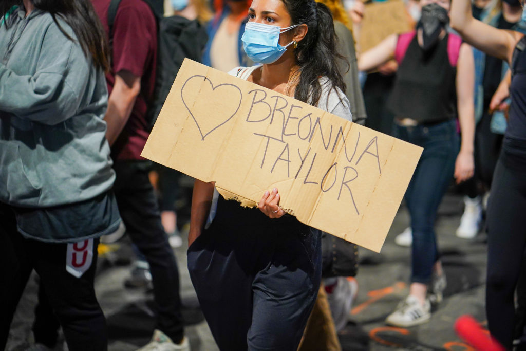 A protester holds a placard expressing her opinion during...