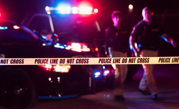Two police officers behind crime scene tape