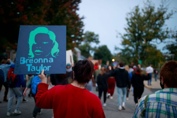 A protester holds a placard while marching during the...