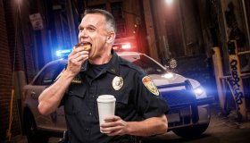 Police Officer Eating Donut in Alley