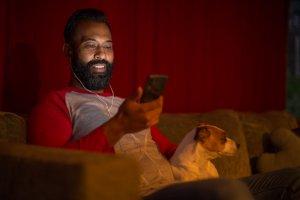 Mixed race man looking at smart phone at home during lockdown