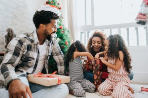 Family celebrating Christmas at home with gifts