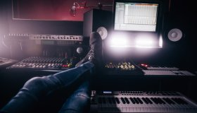 Music producer relaxing with feet up in music recording studio