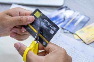 Man cutting credit card with scissors.