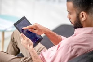 Mixed race man using a digital tablet to check cryptocurrency graphs