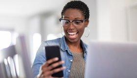 Smiling woman looking at smart phone at home