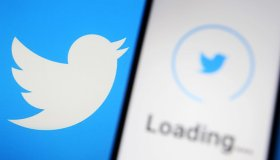 In this photo illustration a Twitter logo is seen loading on...