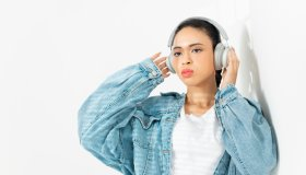 A woman listening to music with headphones.