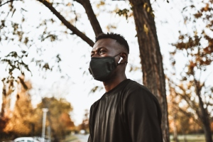 African Male Walking In Park With Face Mask And Listening To Music