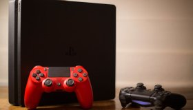 A Sony PlayStation 4 video game console with a red and black...