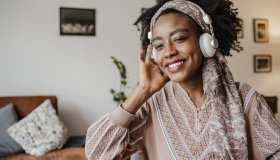 African-American woman is listening to music at home