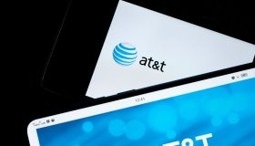 In this photo illustration, AT&T logos seen displayed on...