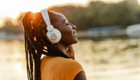 Young African American woman outdoors on sunset and listening music