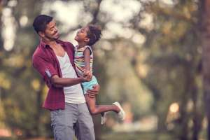 Happy African American father dancing with his cute daughter outdoors.
