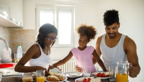 Young happy African American family having breakfast at home