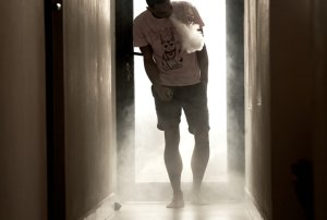 A Young Man Of African-American Descent Is Standing In A Hallway, Blowing Vapour Of His E-Cigarette